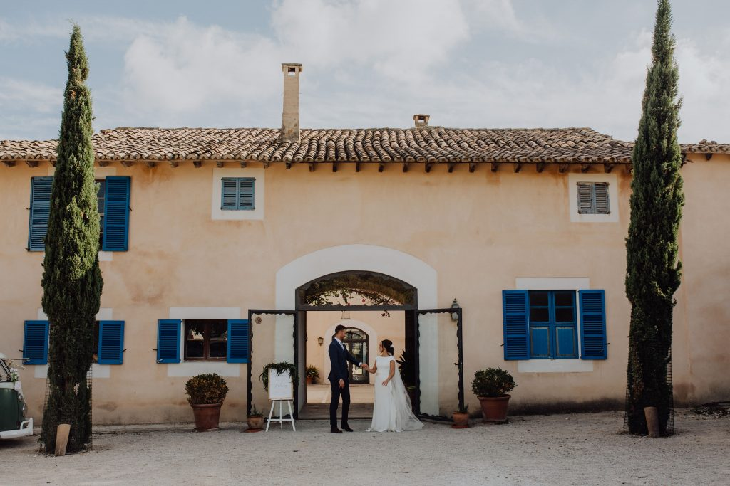 married couple standing in front of Finca Biniorella just after their wedding