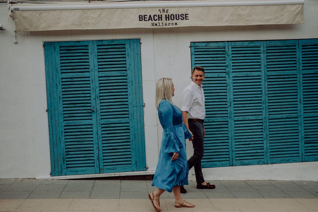 Couple walking past blue shutters in sant Elm Mallorca
