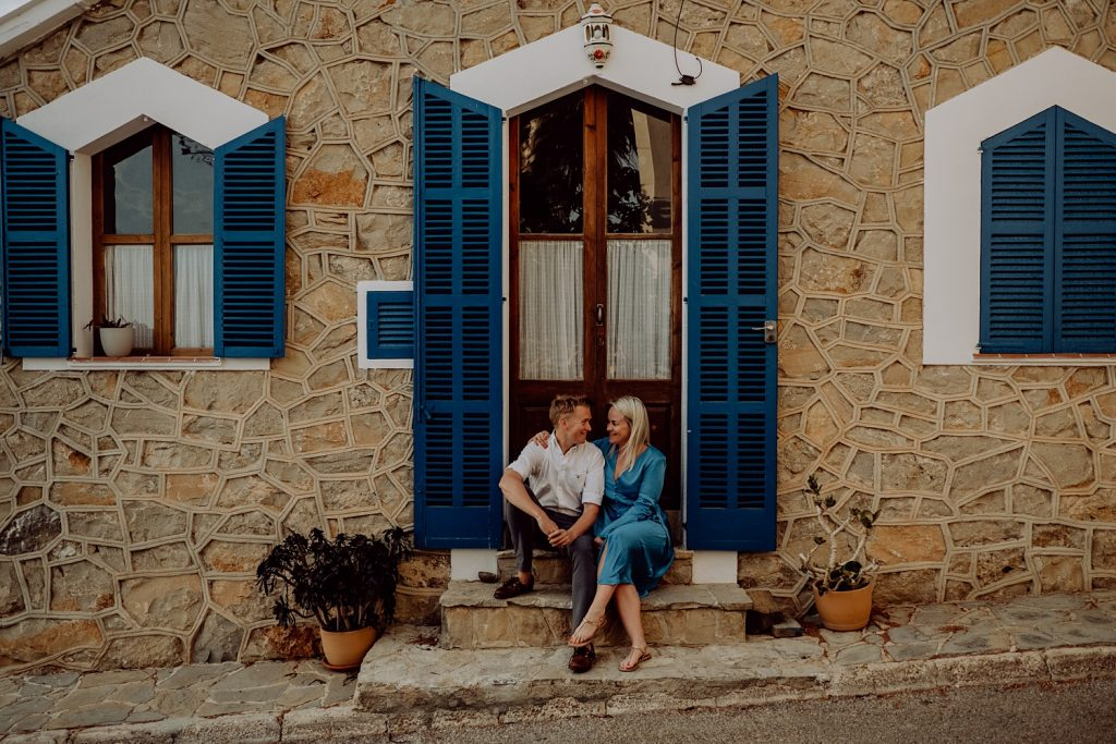 Couple sitting outside a house with blue shutters in sant elm mallorca
